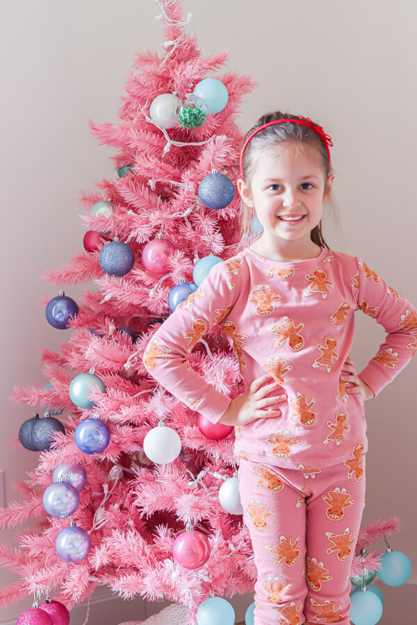 little girl in ponytail and gingerbread pajamas standing in front of decorated Pink Christmas tree