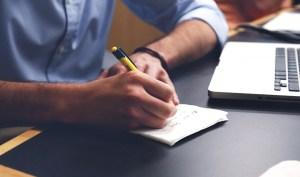 homem-escrever-papel-caneta-portatil