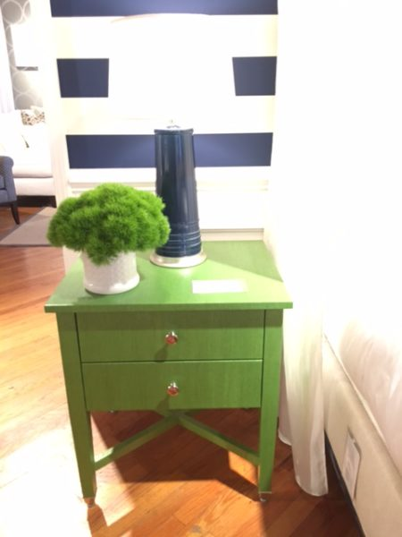Glossy finished emerald green nightstand with navy lamp against wide bold navy and white stripes