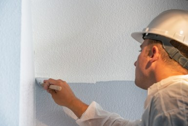 man painting interior of house