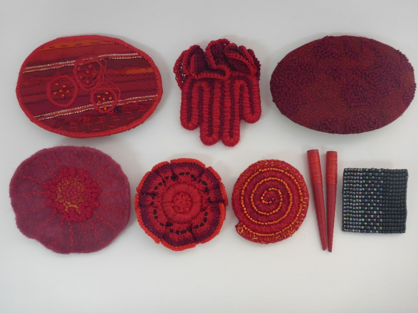 Clockwise from top left: Hair barrette (machine & hand stitching), brooch (wrapped wire, stitching and crochet), hair barrette (hand embroidery), loom-woven beaded brooch backed with leather, experimental paper beads, brooch (wrapped wire with beads and embroidery), brooch (crochet and embroidery), felted brooch with embroidery.
