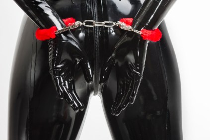 BDSM 101: Safe Sane and Consensual A depiction of a person in latex while wearing handcuffs.  Blogpost by Liz BlackX