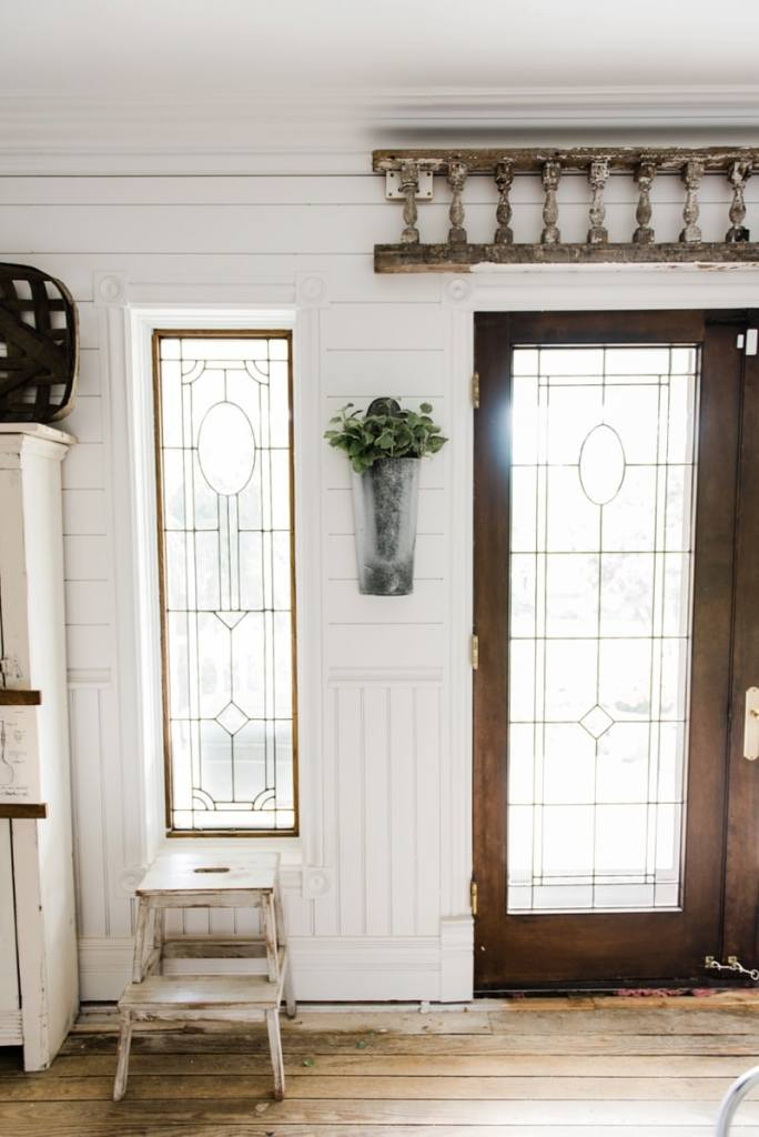 Hanging metal vases with flowers hanging on each side of the french doors. Great farmhouse decor style tips & tricks. A must pin for cottage style and farmhouse style decor. Metal flower vases from Magnolia Market
