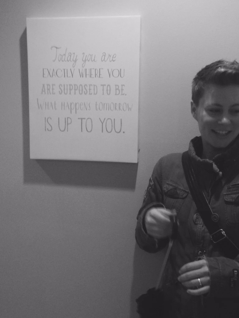 Lizzie Allan stands next to an inspirational quote- self-worth
