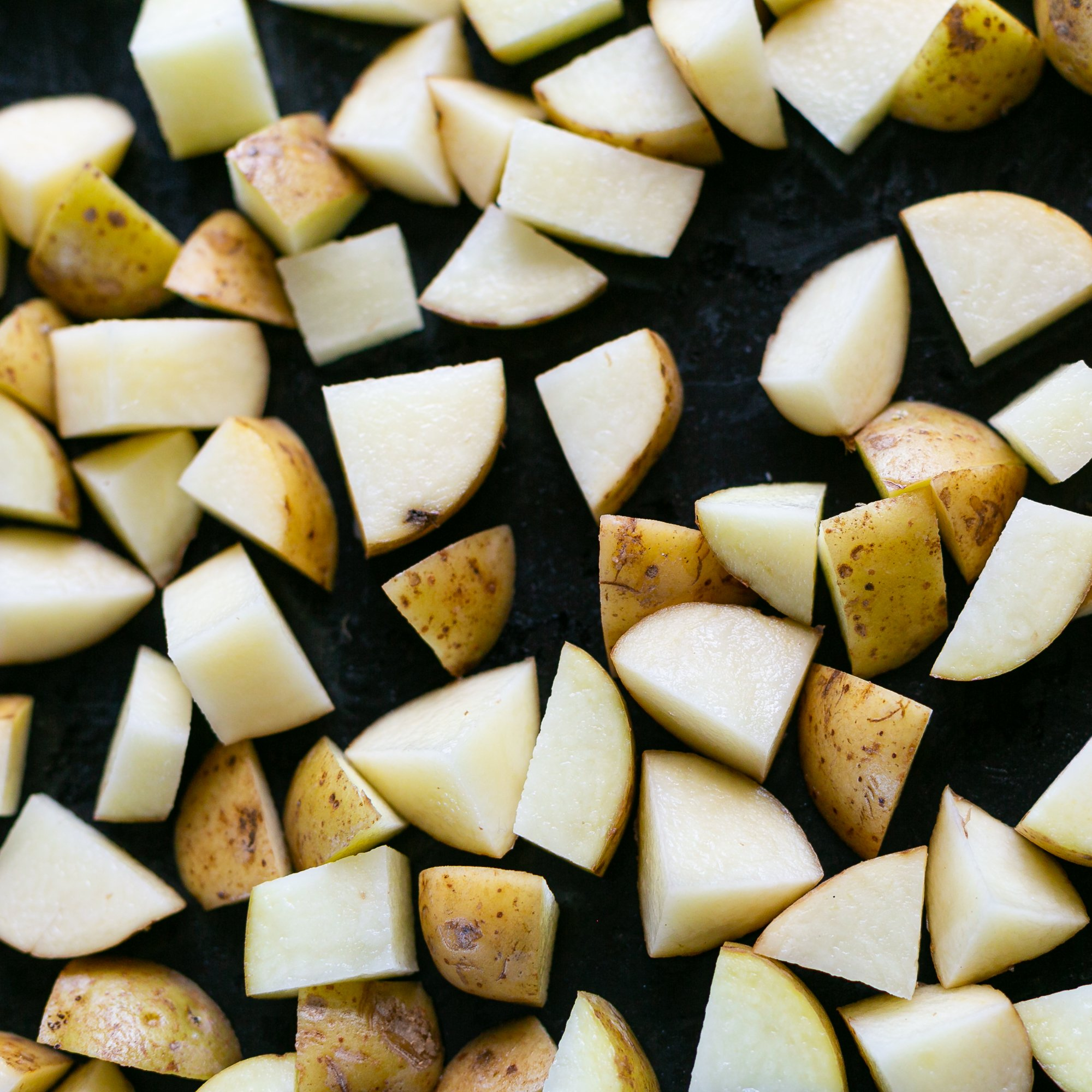 chopped potato on a baking sheet for easy homemade oven chips