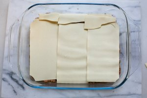 meat and pasta layered in a dish for homemade lasagne