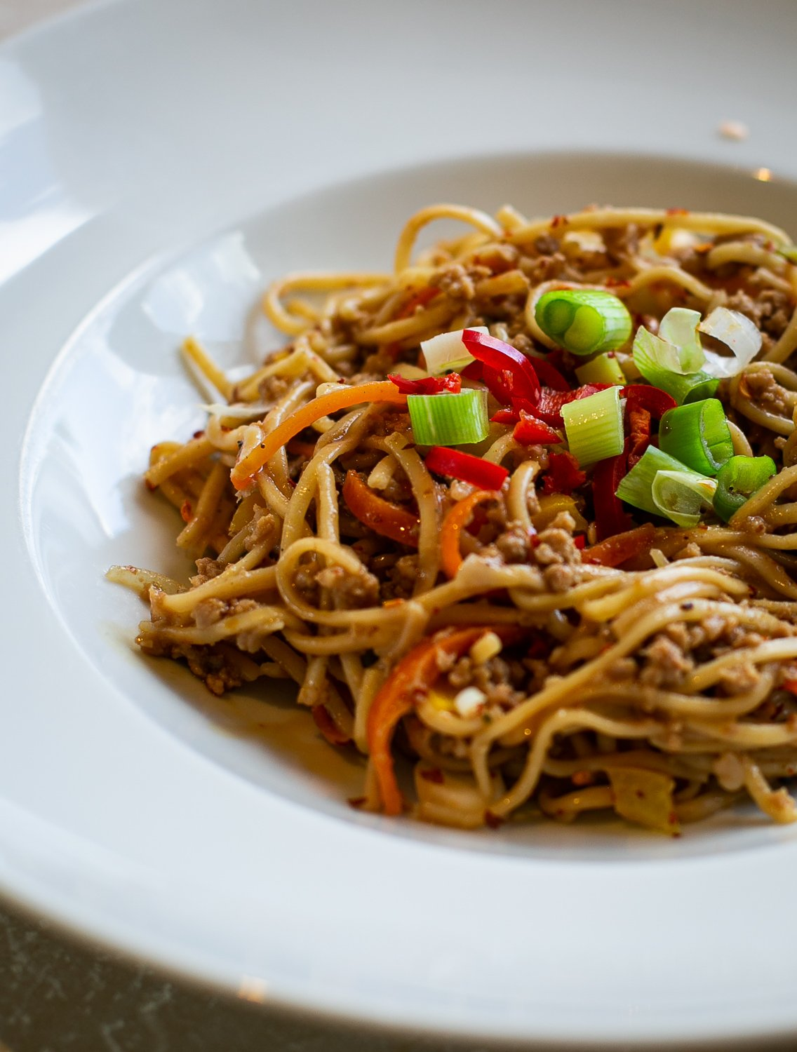 Chilli Pork Noodles with Peanut Sauce served in a bowl with spring onion
