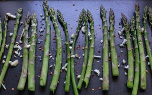 asparagus spears on a baking tray with chilli and garlic