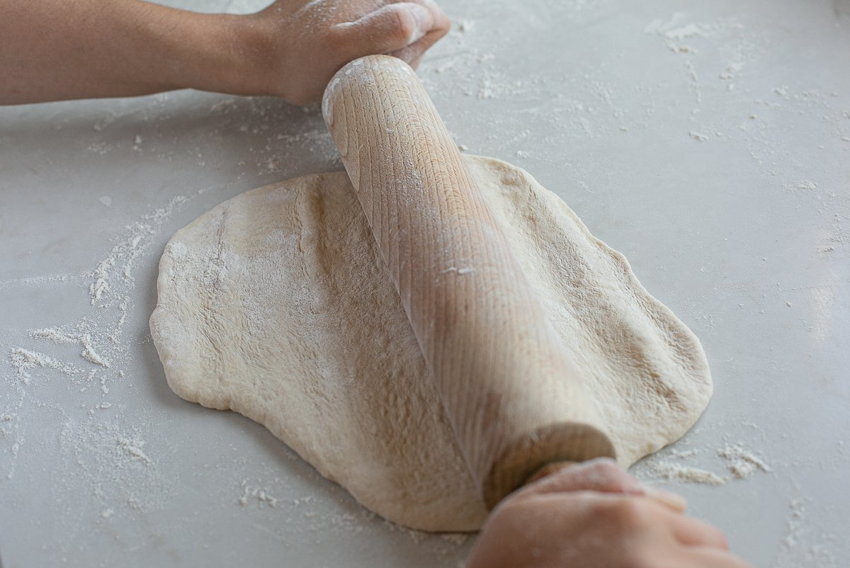maneesh bread dough being rolled into shape with a rolling pin