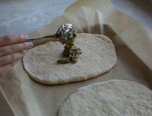 sesame herb mixture being spread onto maneesh bread dough