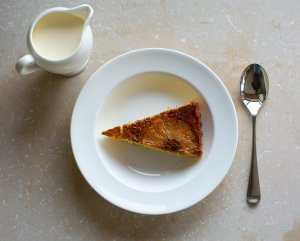 a slice of pineapple sponge in a bowl served with cream