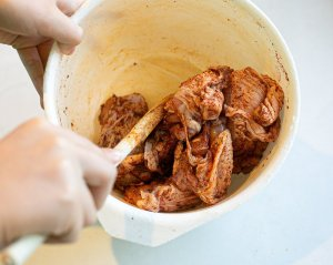 Chicken thighs and spices mixing in a bowl to make special chicken