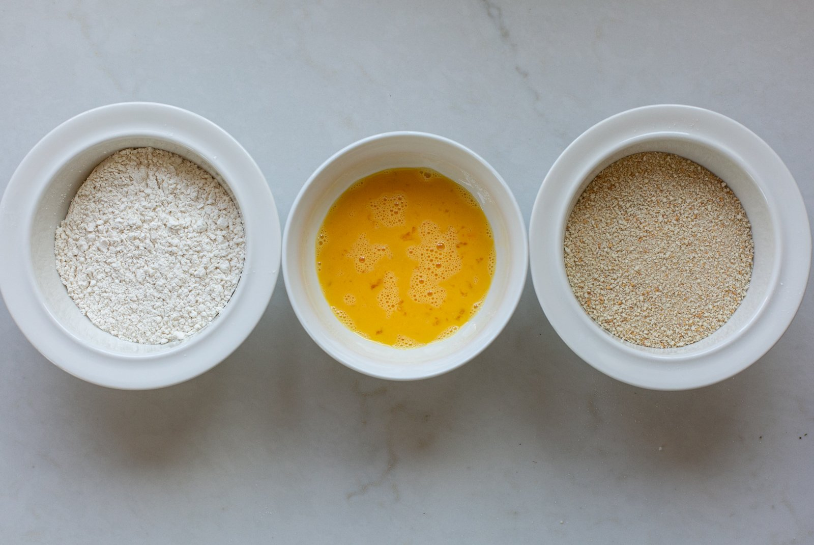 Flour, egg and breadcrumbs in bowls ready to coat chicken fillets
