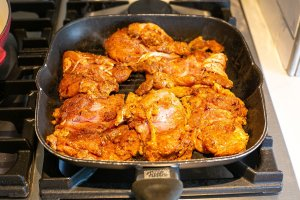 marinated chicken thighs cooking on a griddle pan
