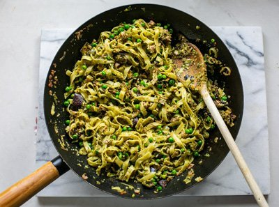freshly cooked aubergine pesto pasta in a wok