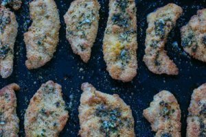 crispy garlic chicken dippers on a baking tray