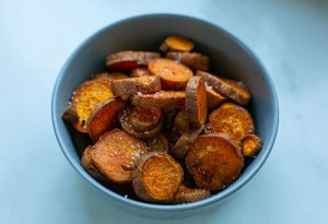 Freshly cooked paprika coated sweet potato fries in a bowl with sea salt