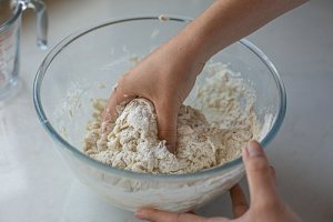 maneesh bread dough being mixed. by hand in a bowl