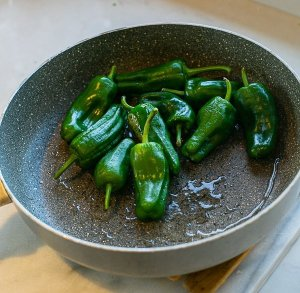 padron peppers cooking in olive oil