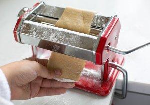 fresh pasta dough being rolled in a pasta machine