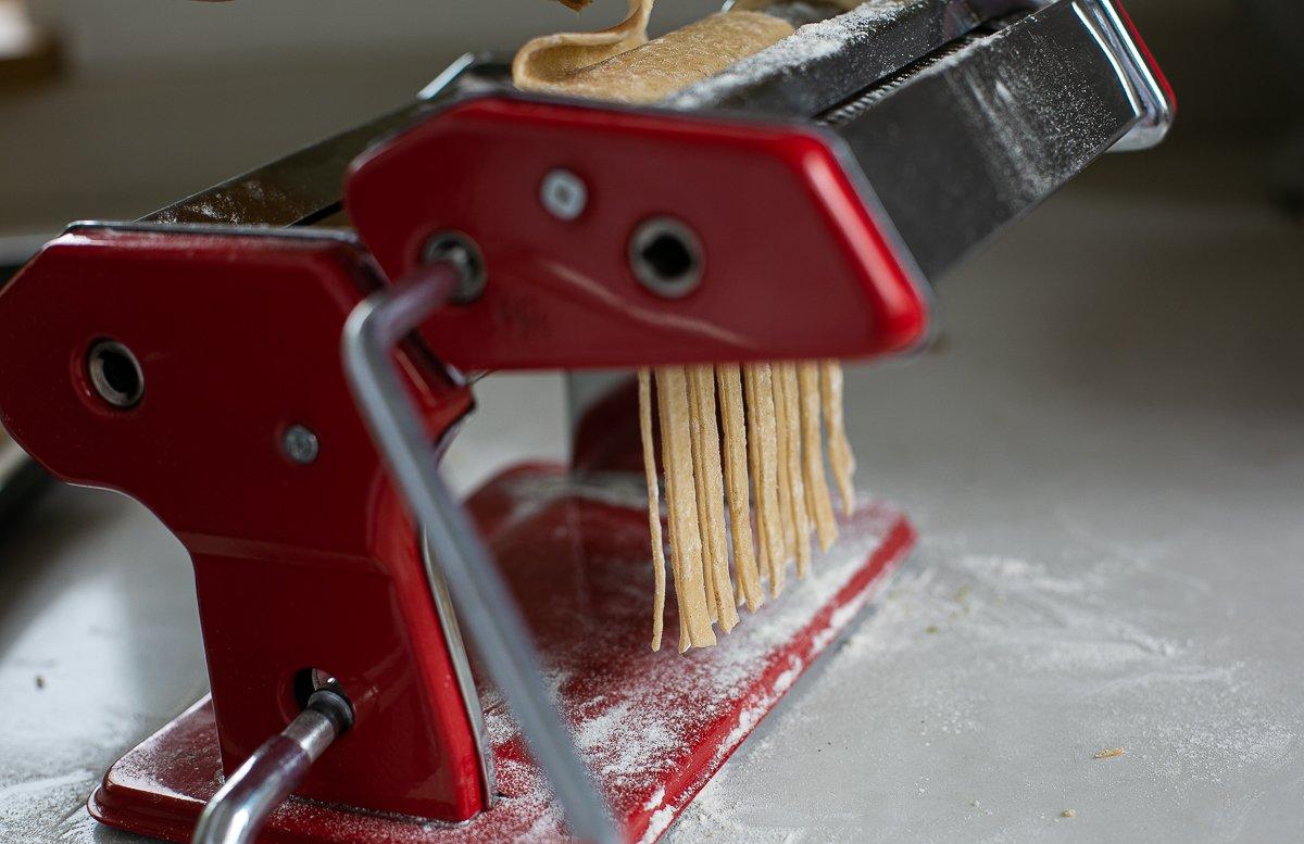 rolling pasta dough through an attachment to create tagliatelle