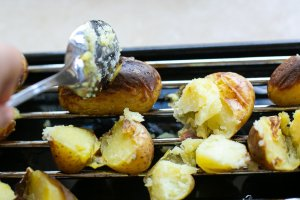 grilled potatoes being chopped with a spoon