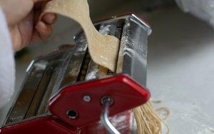 pasta dough being cut into spaghetti