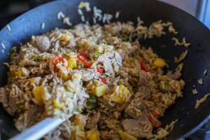 pork and pineapple stir fry cooking in a wok