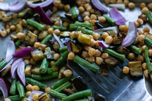 Roasted aubergine, green beans, chickpeas and red onions on a baking tray
