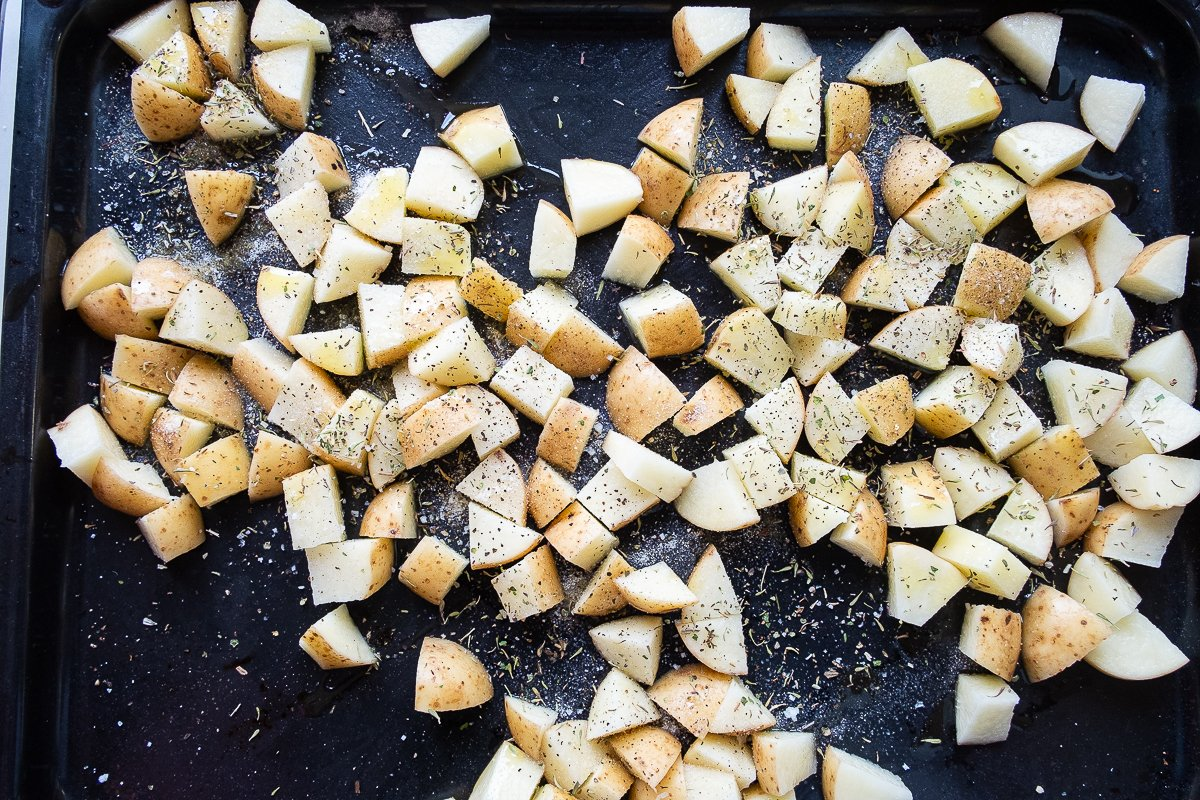 seasoned chopped potatoes on a baking tray