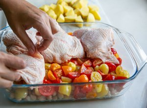 chicken thighs being added to a casserole dish