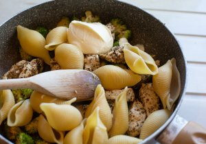 the ingredients for chicken broccoli pasta cooking in a pan