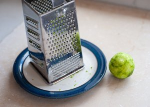 a lime being grated in a box grater