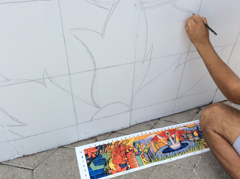 Nicholas Gauthier uses pencil to sketch the design onto a large grid based on the color original.