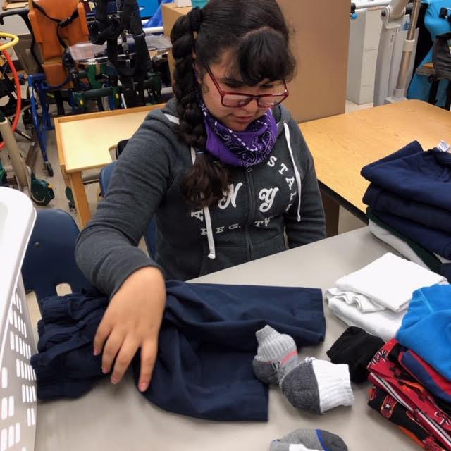 Student Emily Ramirez Arroyo folds clothes