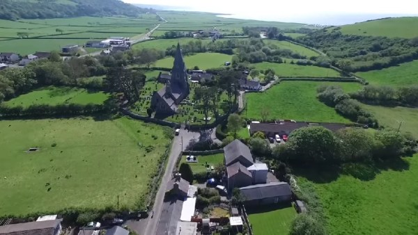 Aerial view of Llanrhystud Church St. Rhystyd, with distant views of the coastline, Ceredigion, Wales.