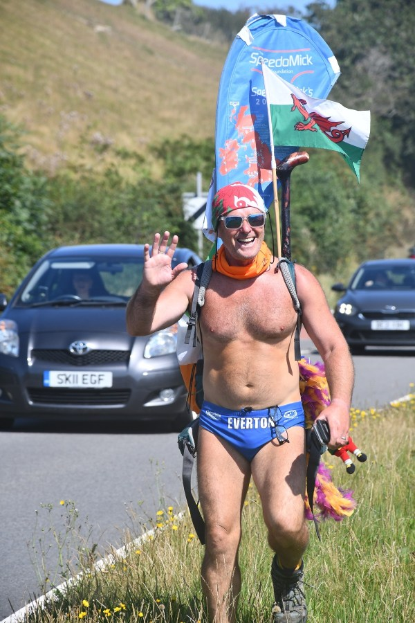 SpeedoMick greets residents as he enters the village