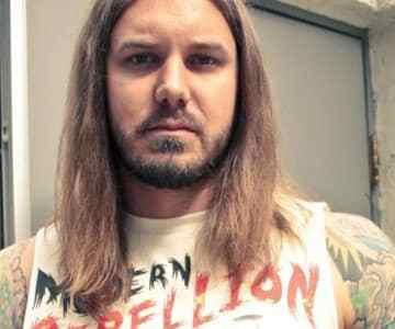 As I Lay Dying frontman Tim Lambesis claims to have developed large breasts due to negligent medical practice…