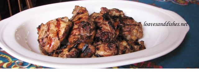 White platter holding 8 grilled jerk chicken pieces