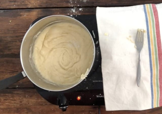 The sauce for cauliflower cheese in a silver pan with towel in background