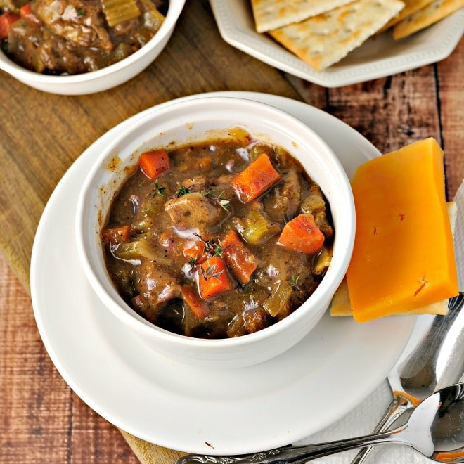 A small white bowl of beef stew sitting on a white saucer with a piece of yellow cheese beside it