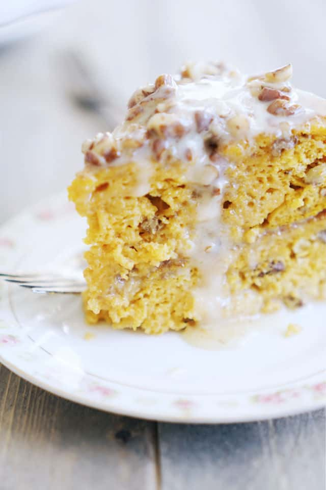 A side view of a slice of pumpkin praline cake showing the tender and moist center with icing running down the side of the cake