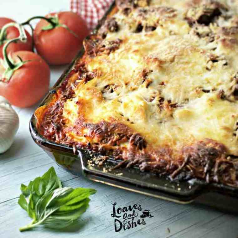 A photo of the crispy browned edges of Cowboy Lasagna with basil leaf and tomatoes