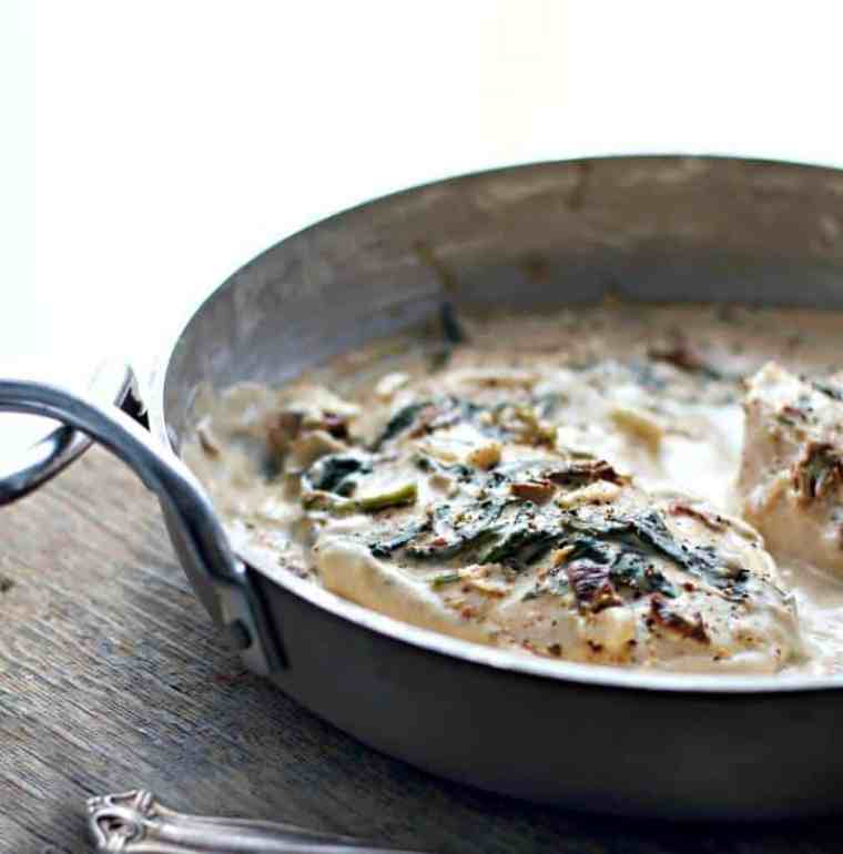silver pan on a wooden background filled with spinach covered meat