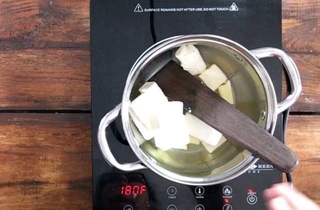 A saucepan on the stove with butter and cream cheese inside and a wooden spoon