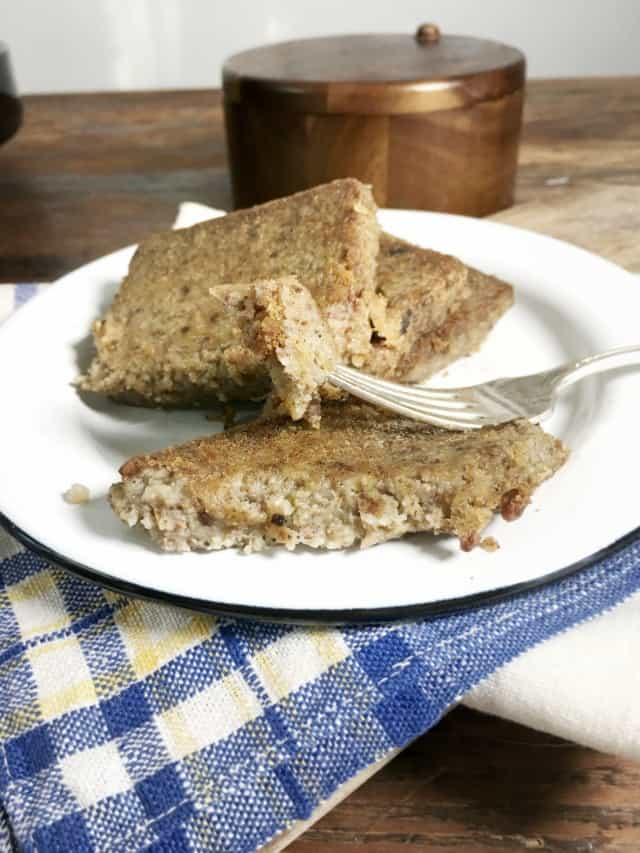 a fork holding a piece of scrapple with two other slices on a white plate