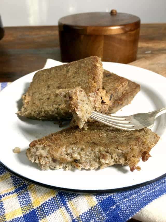 a white plate of scrapple with two slices on the plate and another part slice, fork holding piece