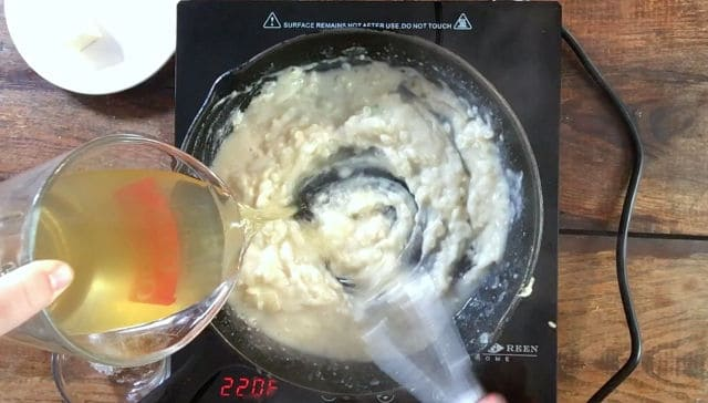 A whisk stirring the mixture in the frying pan while a liquid measure pours stock into the pan for how to make gravy without drippings