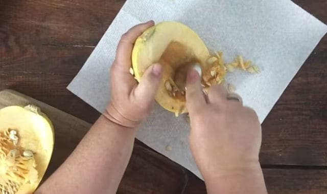 two hands removing the seeds from the middle of a squash