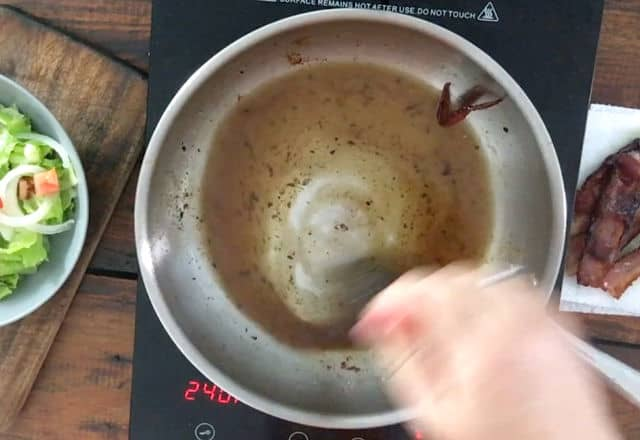 hand whisking bacon grease with other dressing ingredients in frying pan